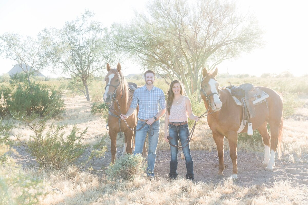 couple standing in between two horses, all looking at the camera