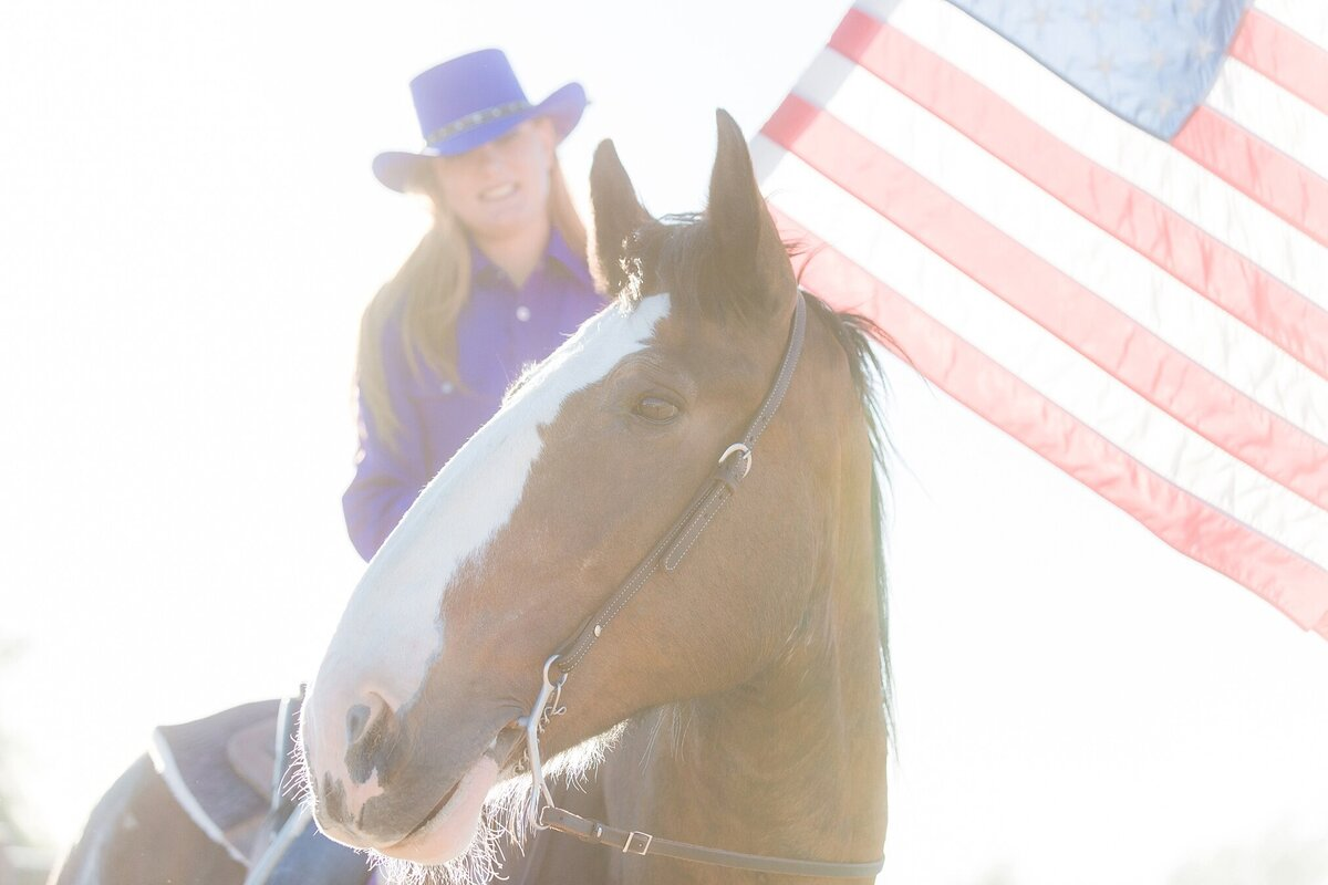 girl sitting on her clydesdale horse while carrying an American flag