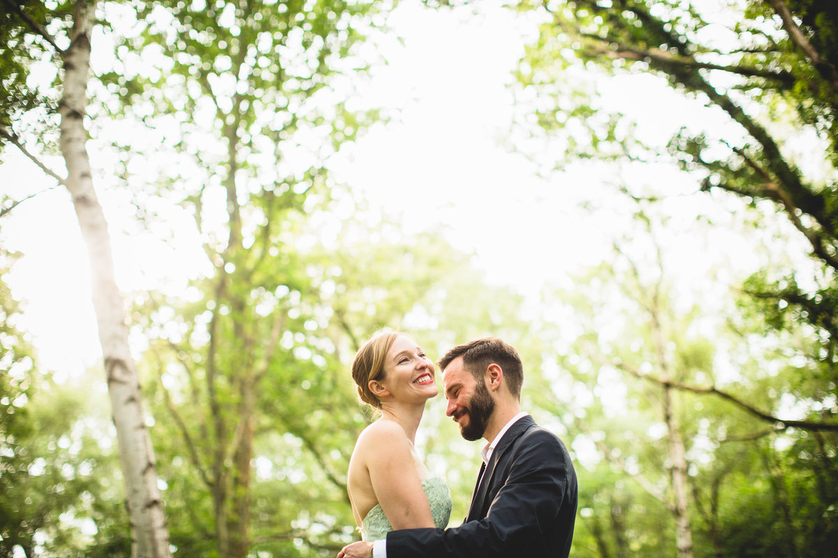 a natural photo of bride and groom taken in the woods