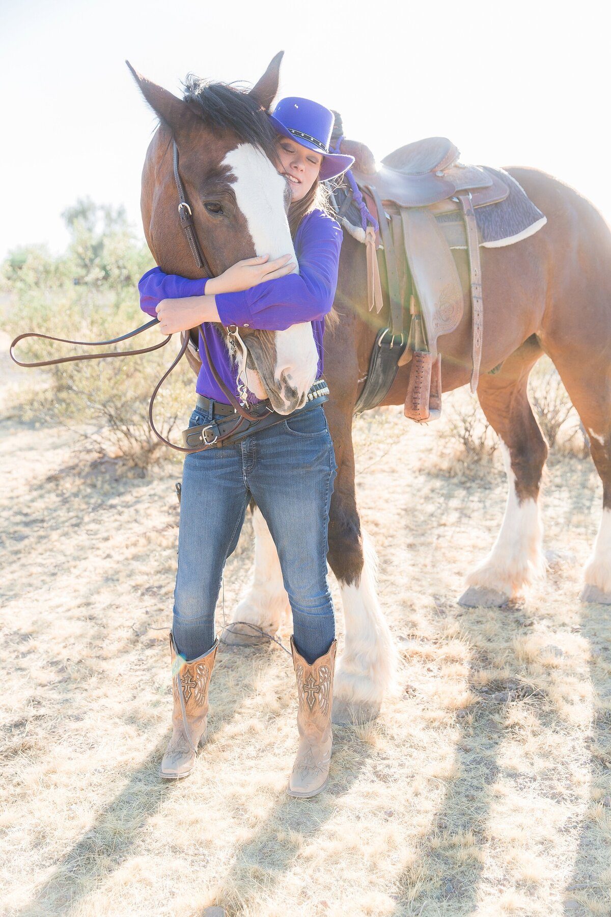 Cowgirl hugging the face of her Clydesldale horse