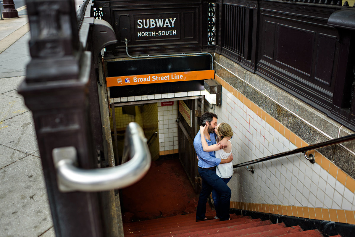 Coming out of the philly subway, a couple stop on the stairs for a kiss.