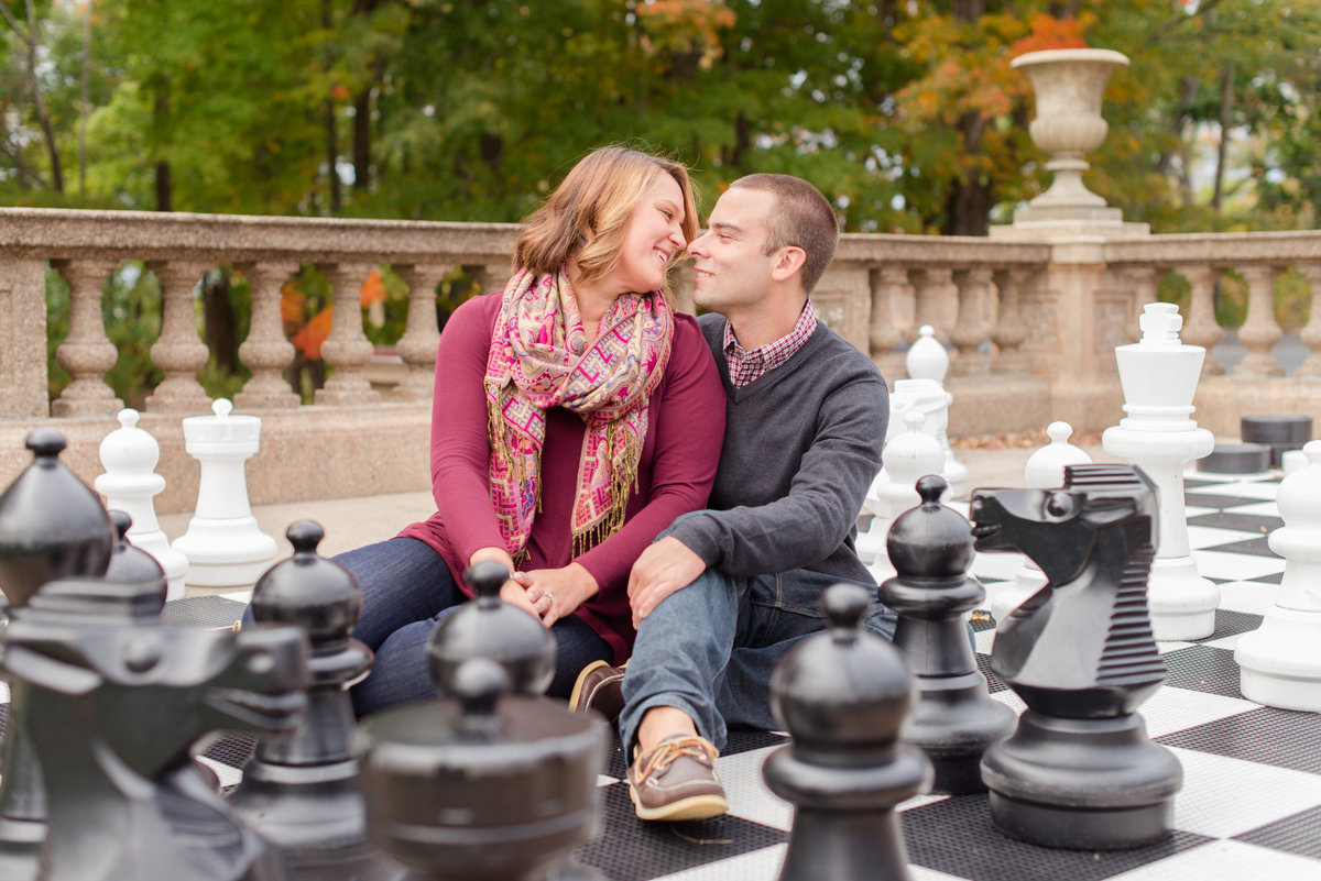 crane estate engagement photos on a life size chessboard