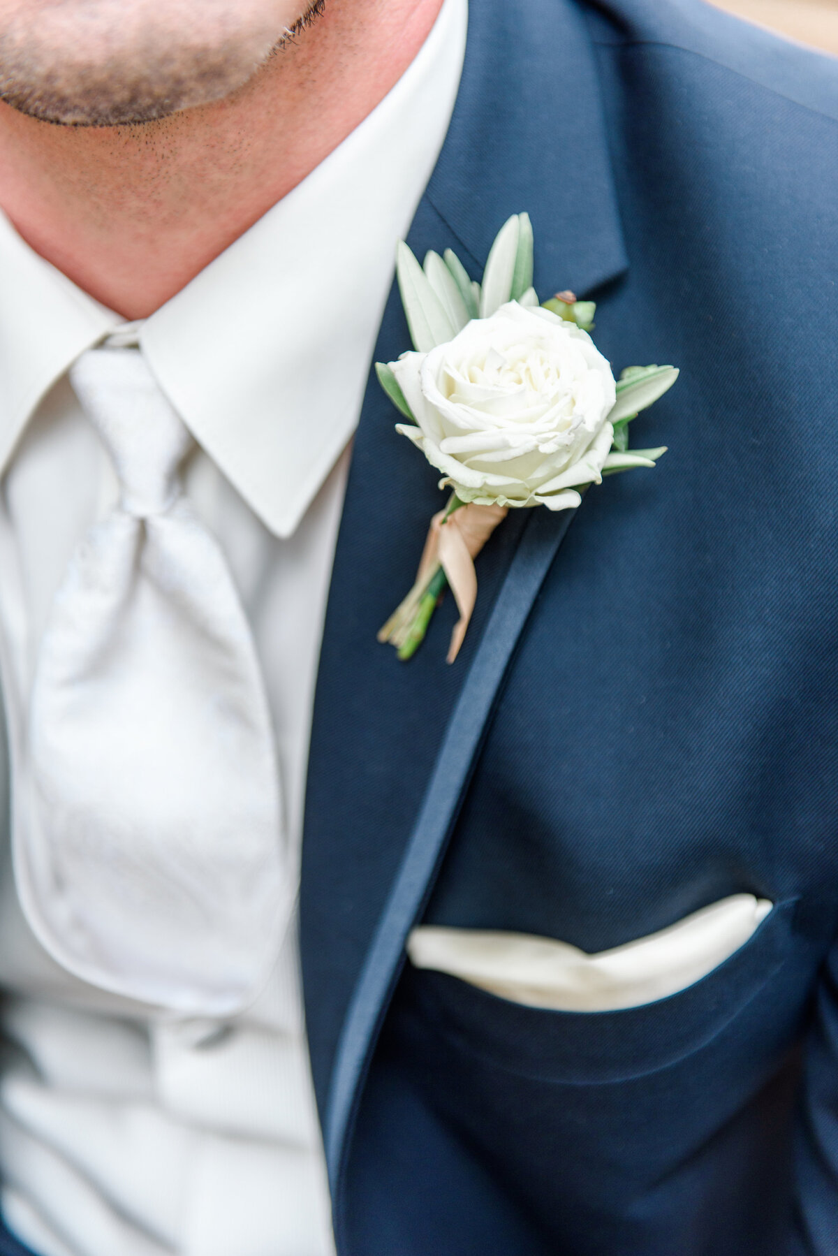 close up of navy tux with boutonniere