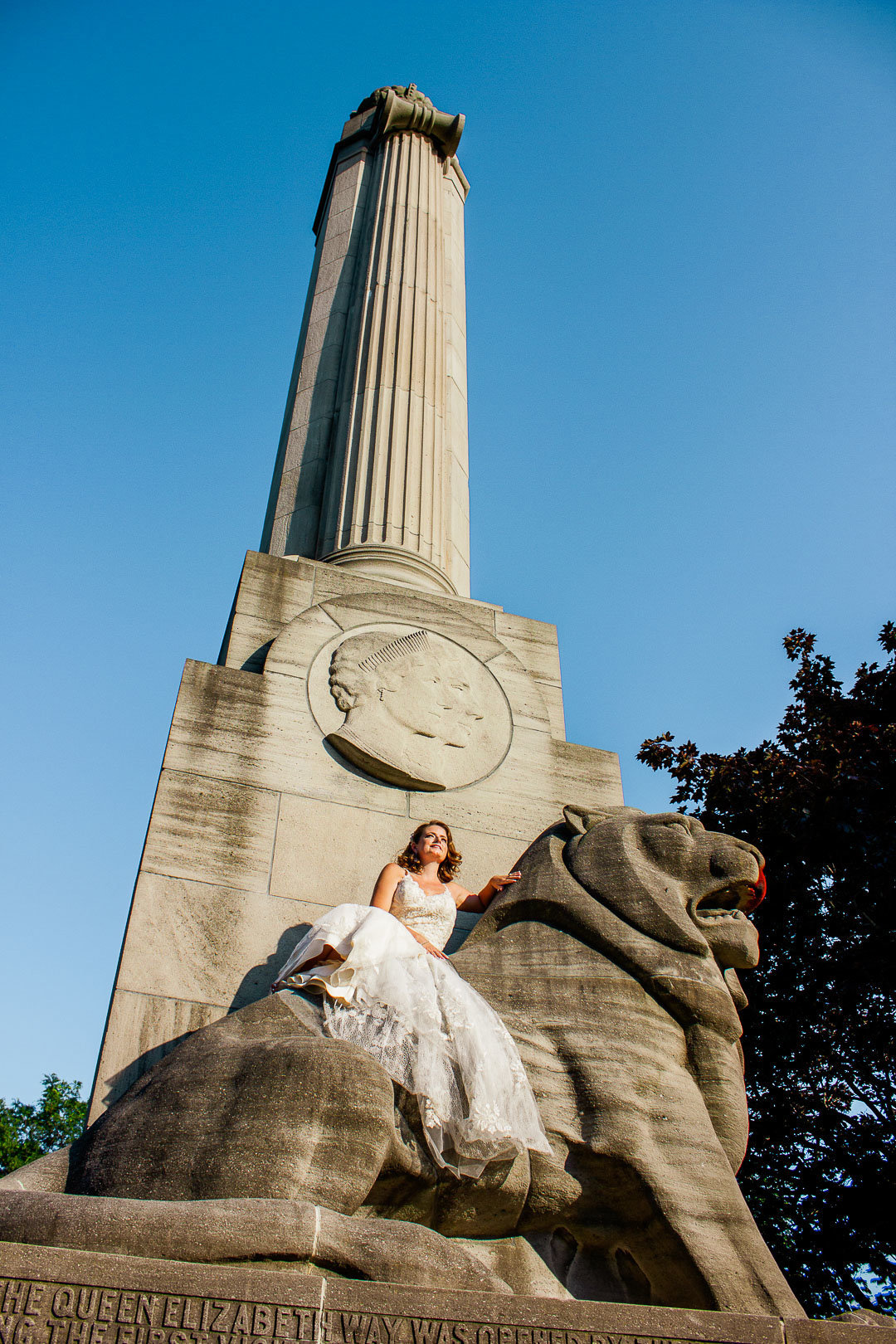 The bride sits proudly on her Toronto Lion Statue at the Toronto Ontario Waterfront Sunnyside Park for Wedding Portrait