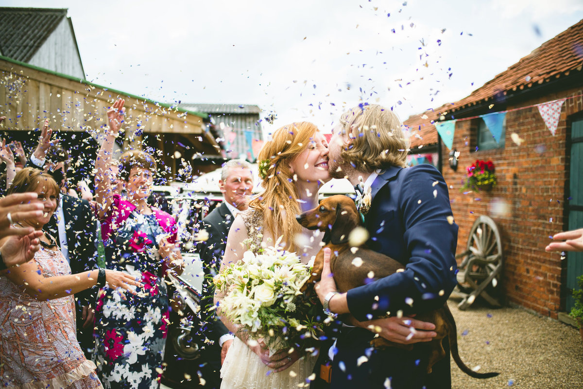 bride and groom holding a daschund and getting confetti thrown at them