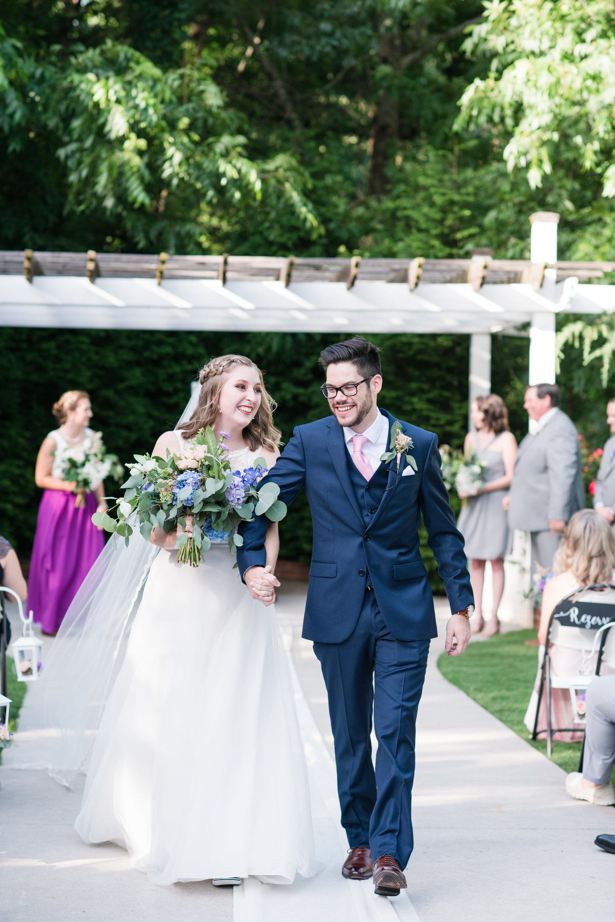 a bride holding a colorful wedding bouquet holding hands with her husband wearing a navy blue suit walking down the aisle after they kissed at Gardens at Gray Gables