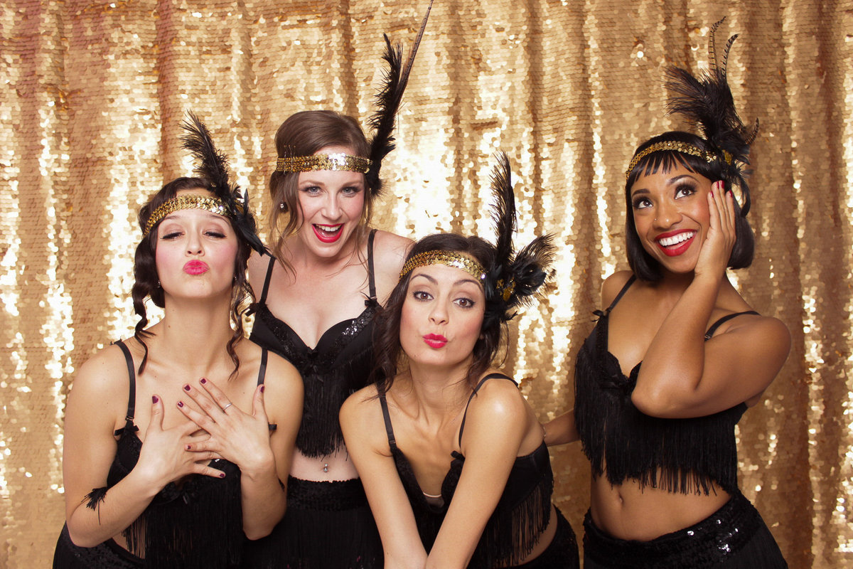 Themed gatsby flapper party guests pose for a photo booth