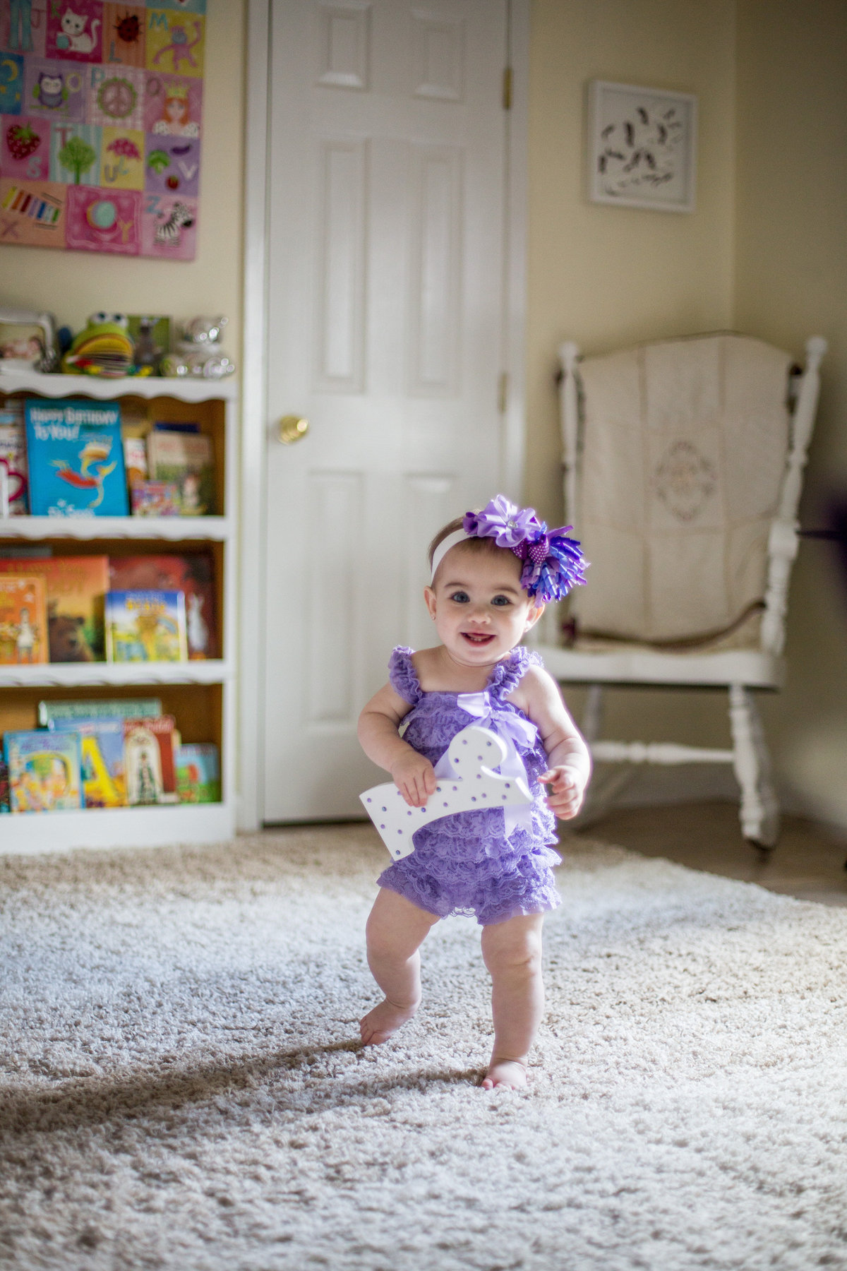 One year old toddler walking in her nursery during an in home photography session in San Antonio.