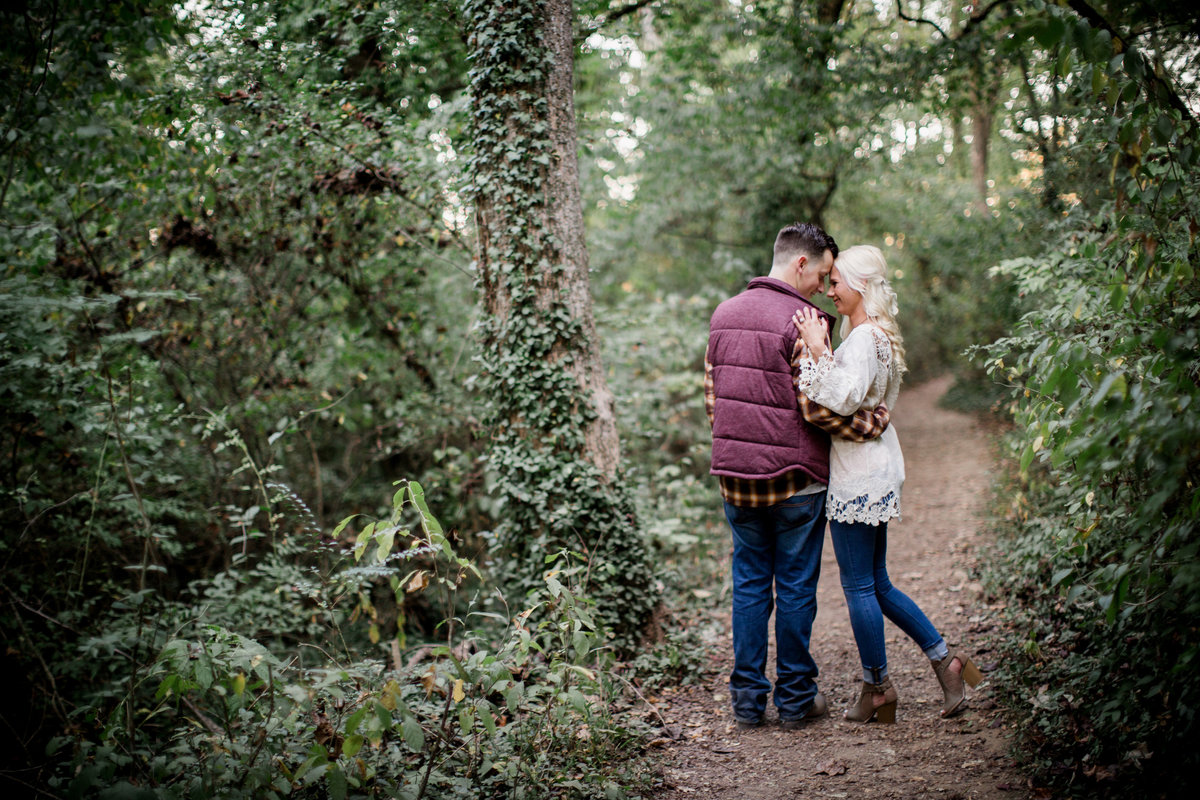 Pulls her waste into his side on a trail at Ijams Nature Center engagement photo by Knoxville Wedding Photographer, Amanda May Photos.