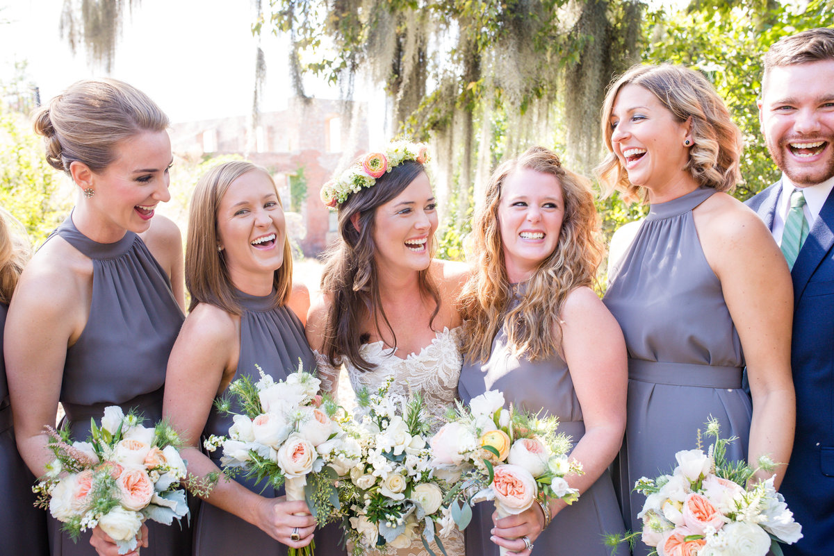boho bride with flower crown smiling with bridal party in lavender dresses