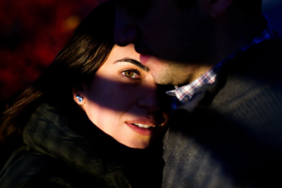 A shadow frames a bride to be's eyes as she lays on her fiance's chest.