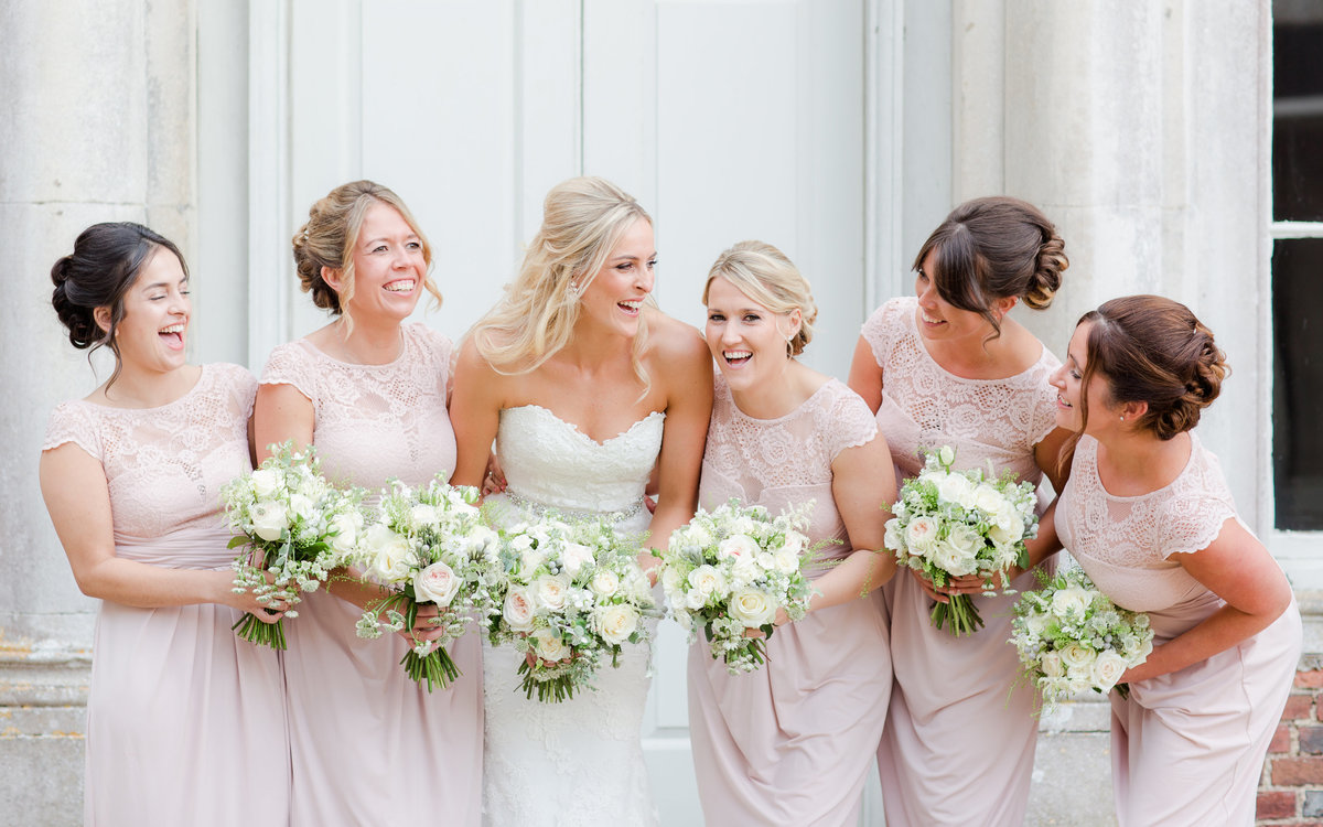 Beautiful bride in Enzoani gown with her bridesmaids in Pastel pink dresses and beautiful natural bouquets  all laughing at Goodwood House wedding venue