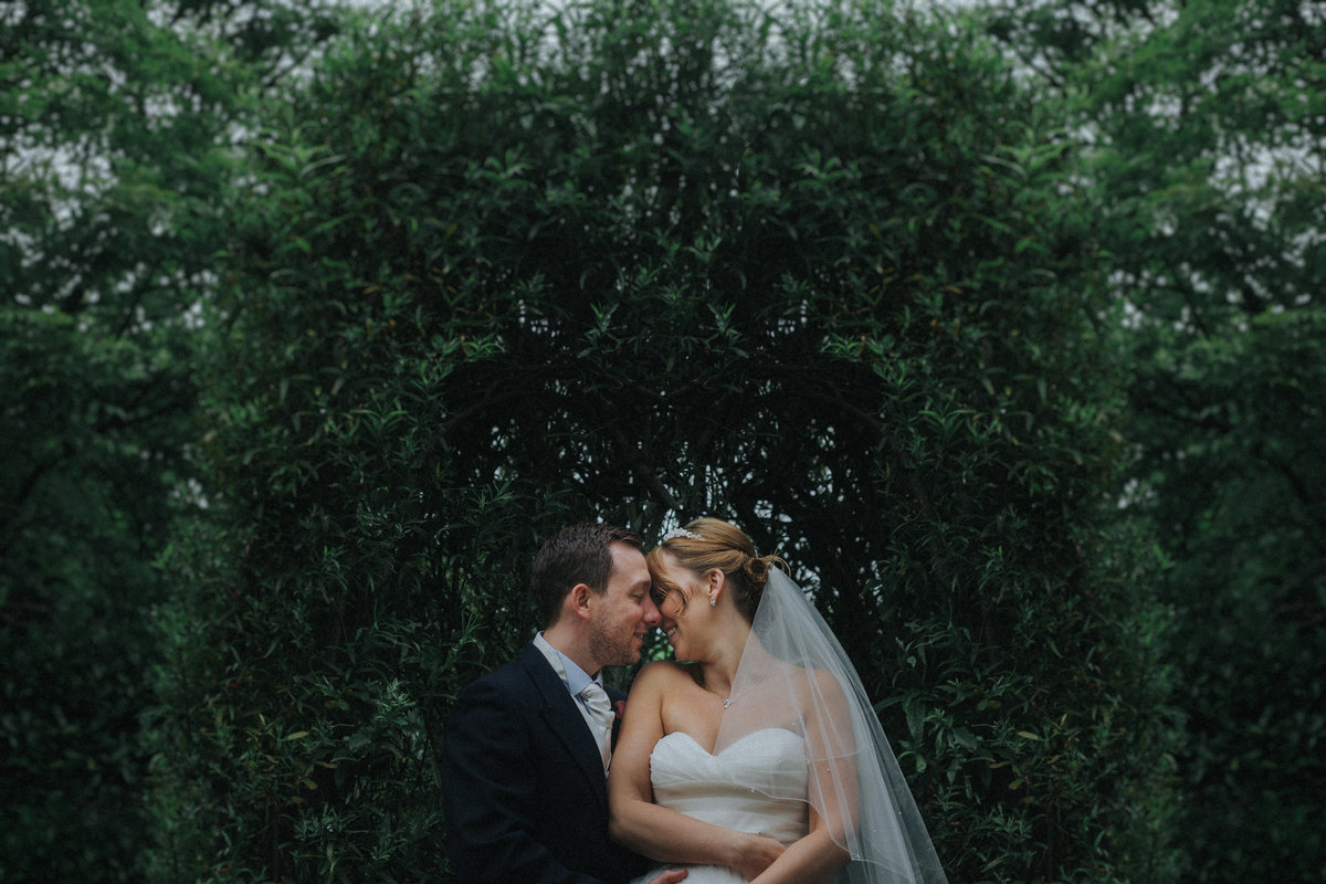 Couple embrace in front of fir trees - Lancashire Wedding Photographer Jono Symonds