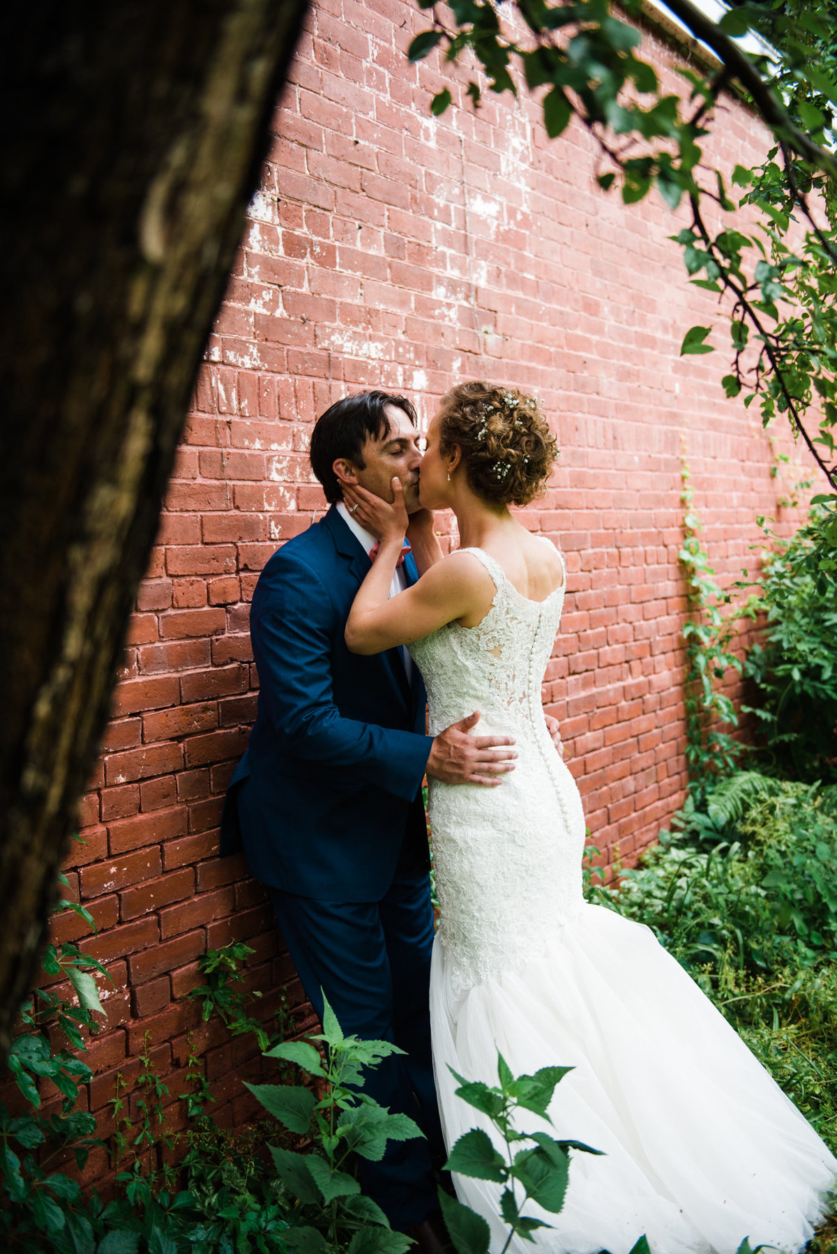 Lyman Estate bride and groom by brick wall