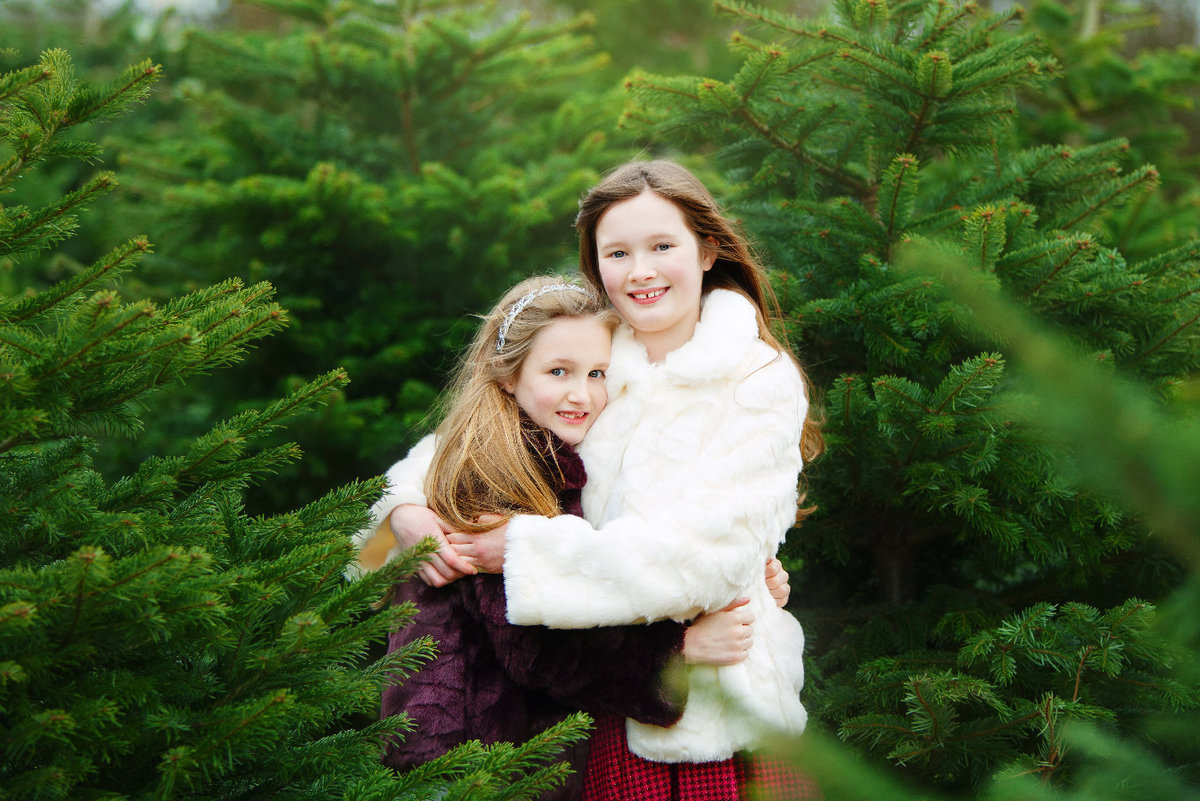 sisters embracing christmas tree