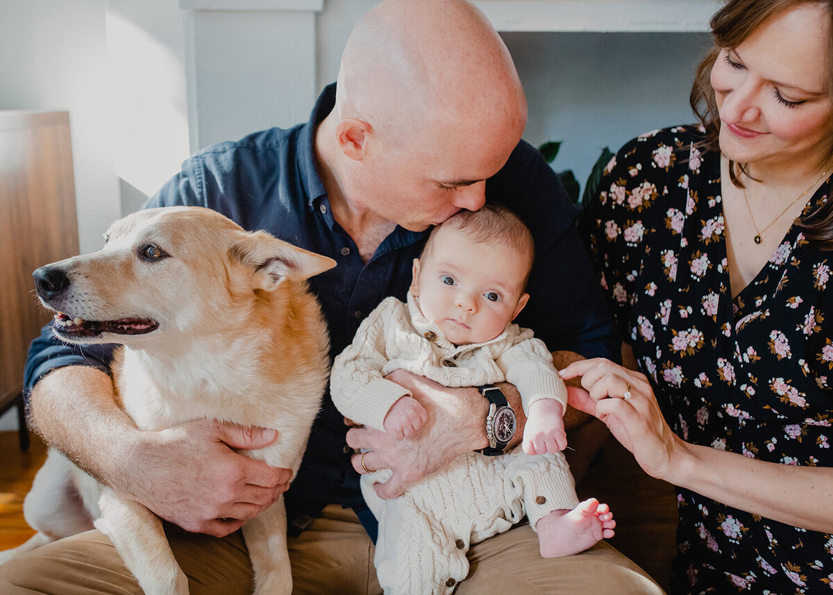 "Newborn photos can include dogs too! A dad hangs onto his infant song and their ""first born"" dog, while mom looks on."