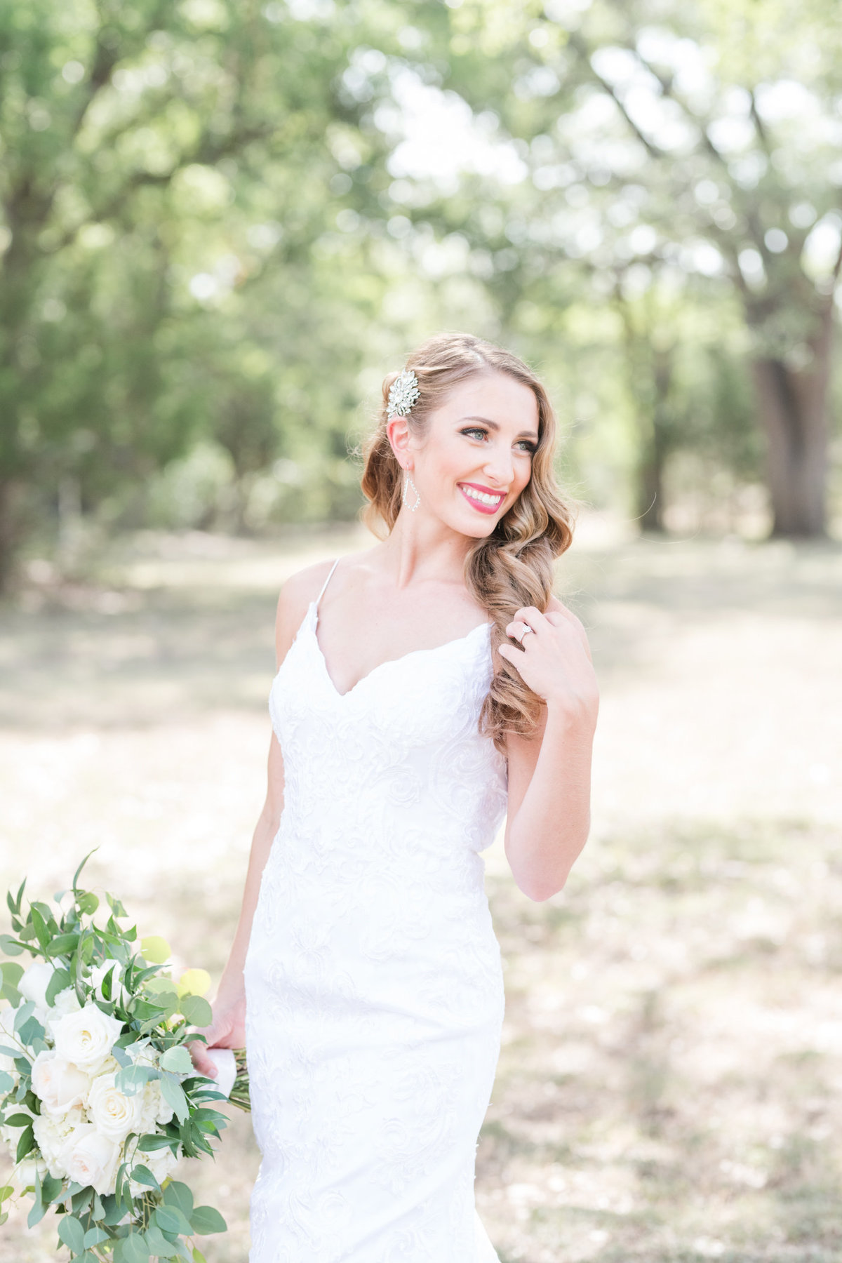 Bride smiles over her shoulder revealing a vintage hair pin while holding a white and green bouquet of flowers at Kindred Oaks in Georgetown Texas