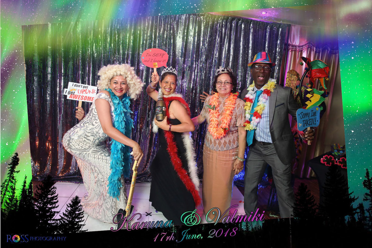 Four older friends wear fun props in front of shiny silver curtain. Photobooth by Ross Photography, Trinidad, W.I..