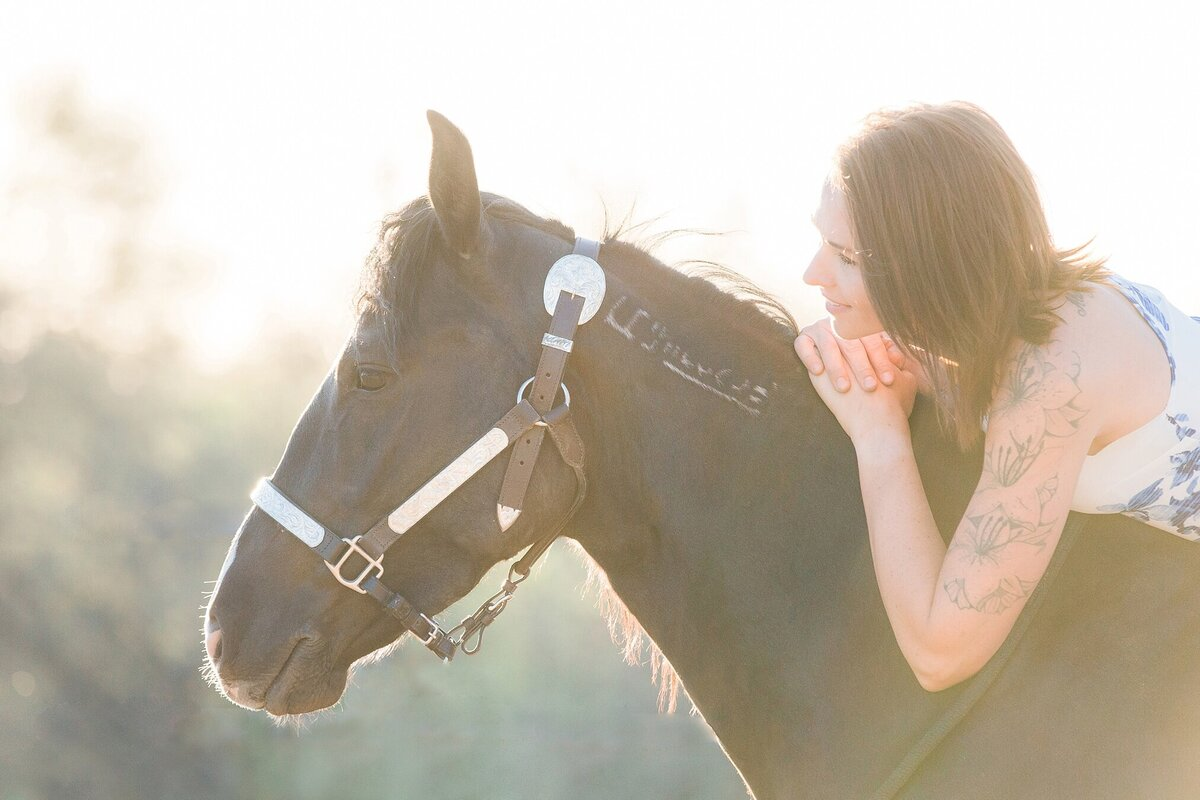 girl laying on the neck of her black mustang horse