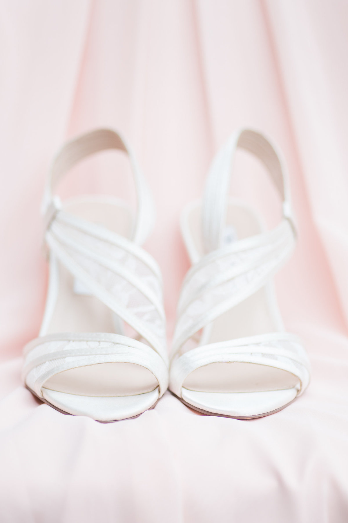 White bridal heels set against blush background