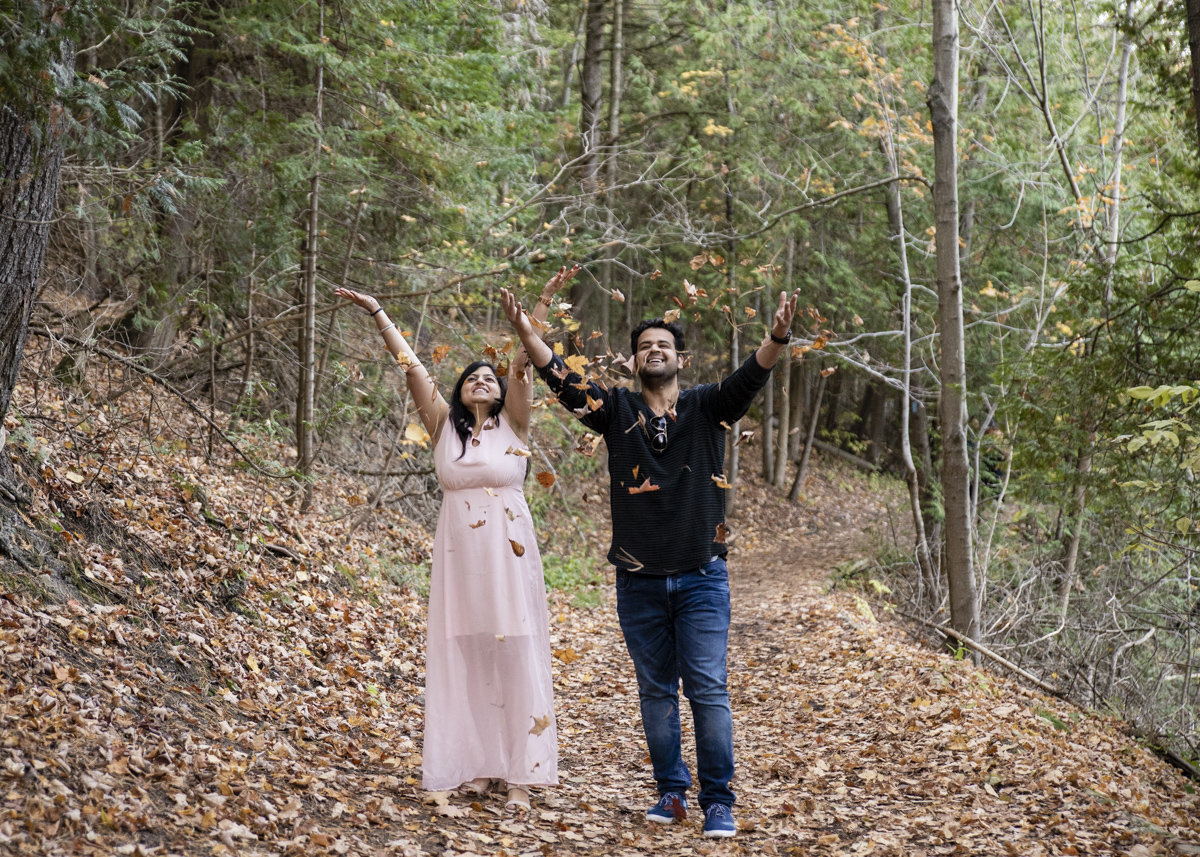 engaged couple throwing leaves in the air at credit valley river provincial park belfountain