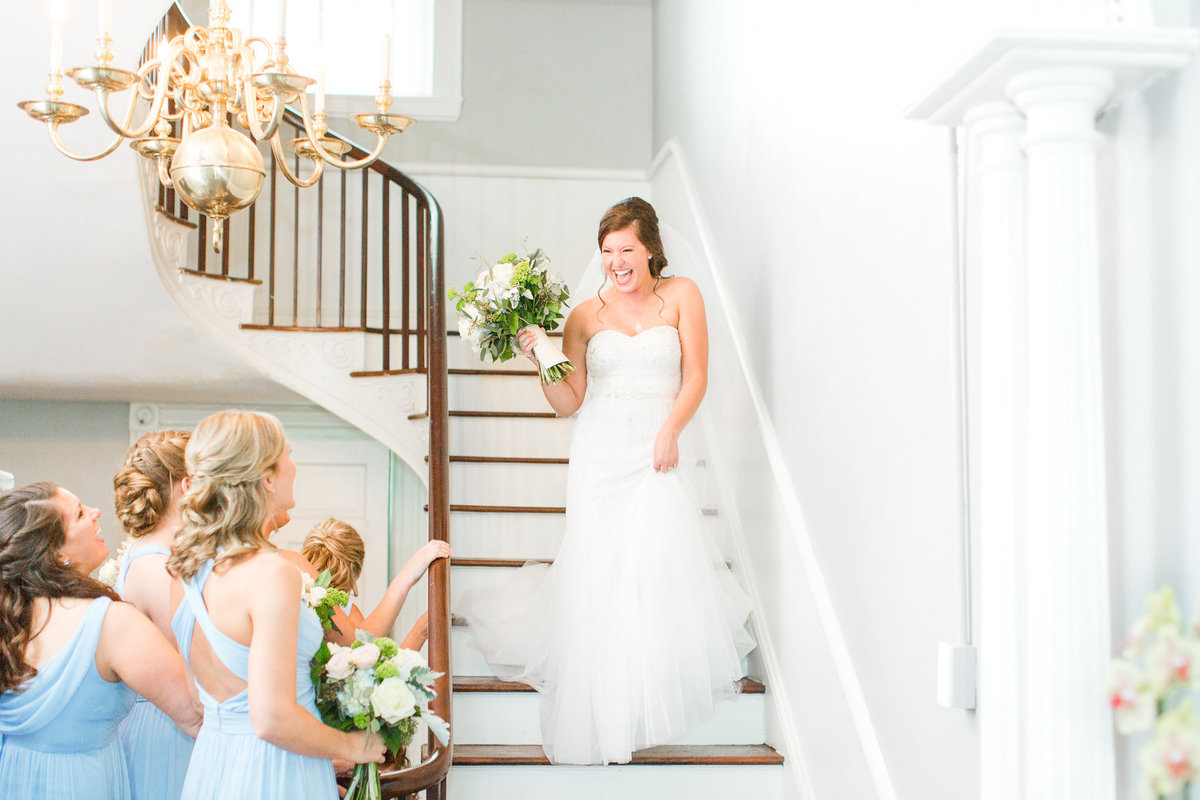 A joyful bride walking down the stairs so her bridesmaids can see her in her wedding dress for the first time.