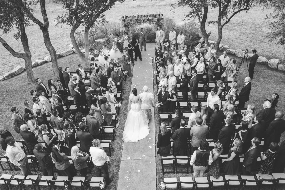 top view of father of bride walking daughter down aisle during wedding ceremony at Vista West Ranch venue in hill country