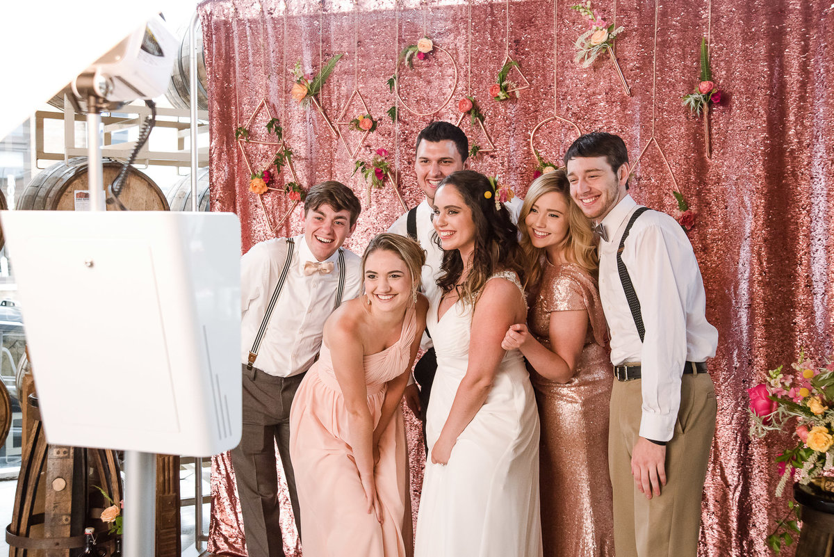 Wedding party uses the photo booth at a wedding with a pink rosé mermaid sequin backdrop and floral attached