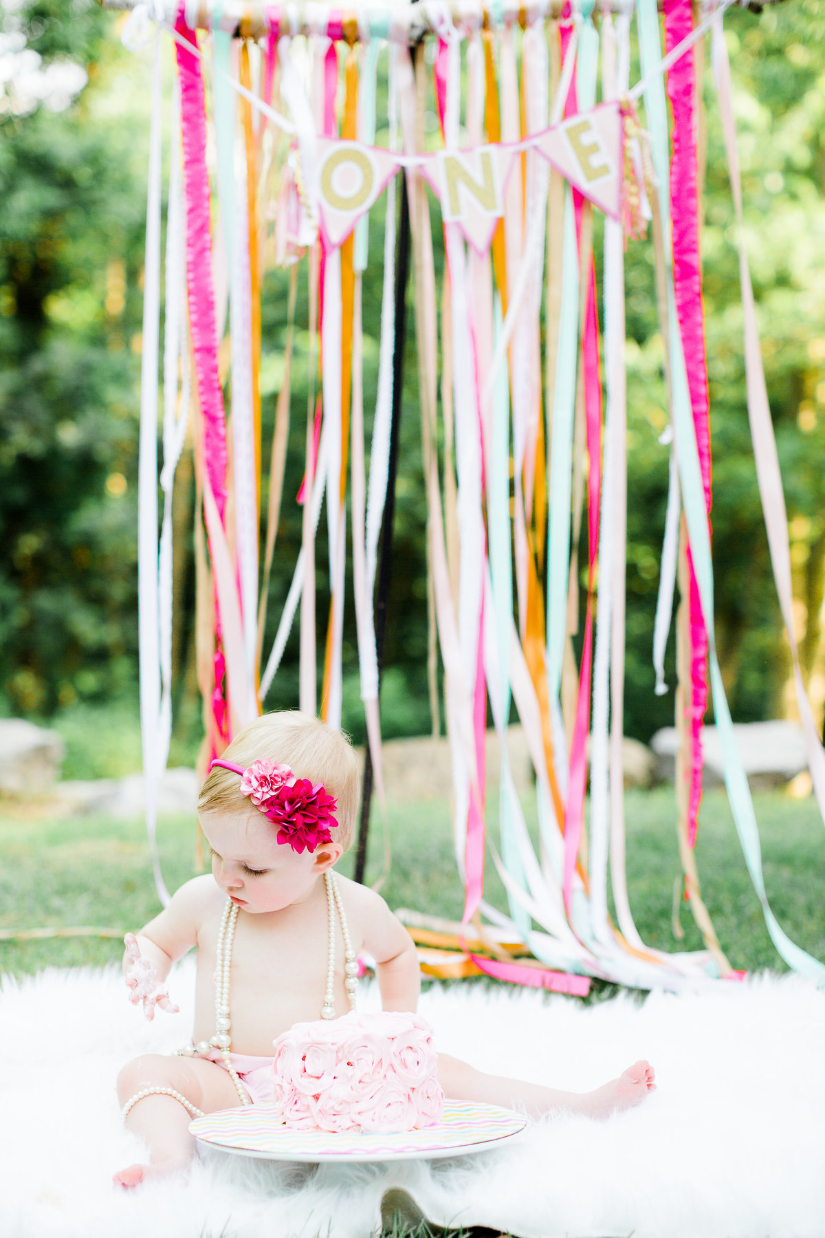 One year old's cake smash session with pink cake pink bow and pink ribbon