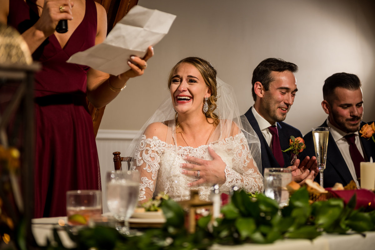 bride reacting to speech by her bridesmaid