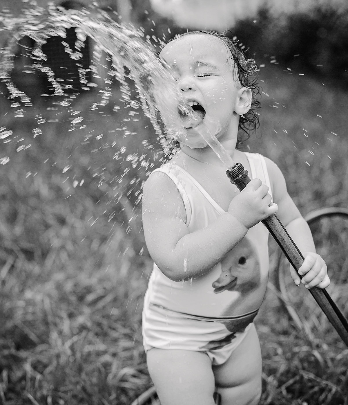 charlotte documentary photographer jamie lucido creates a beautiful and playful image of a small child drinking out of a backyard hose