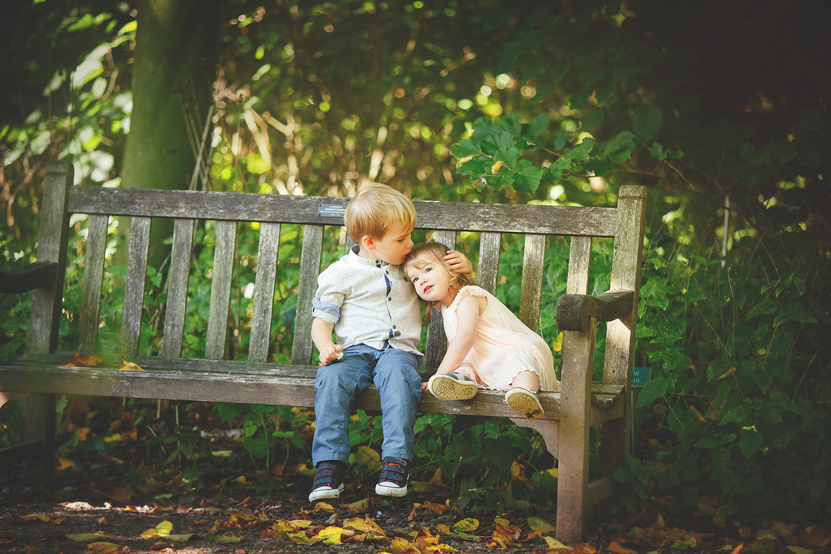siblings cuddling on bench