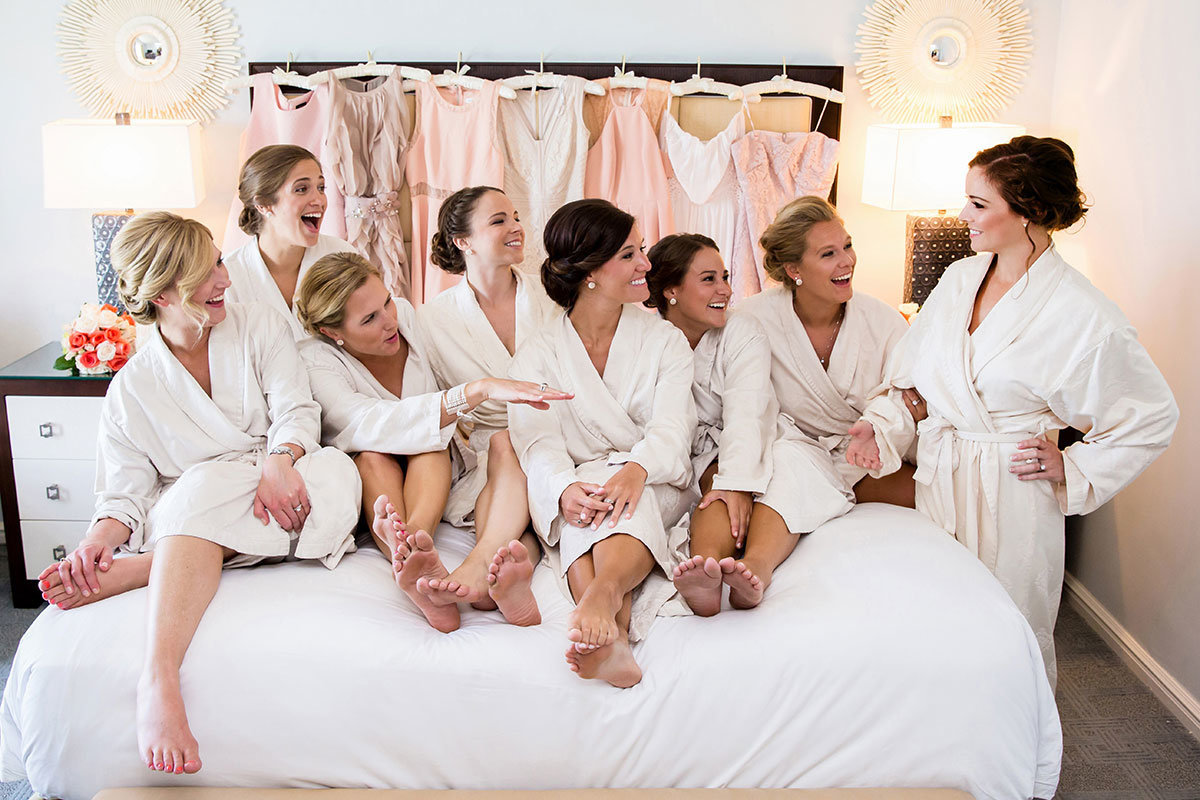 bridesmaids in robes on bed wedding photo