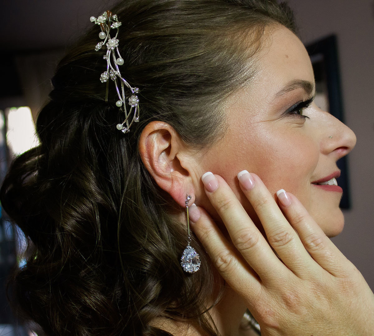 bride profile showing her silver hair jewelry and tear drop sparkling earrings