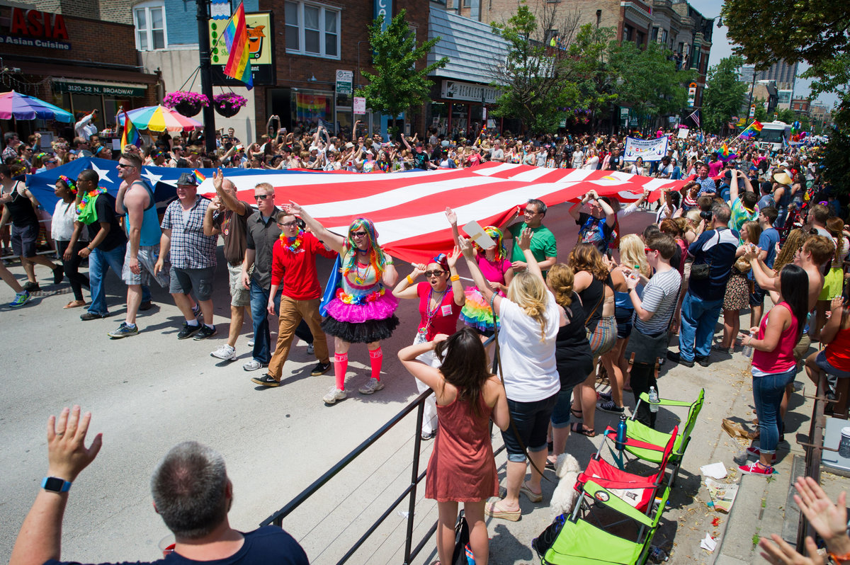 Paraders walk with large flag at Chicago Pride parade.