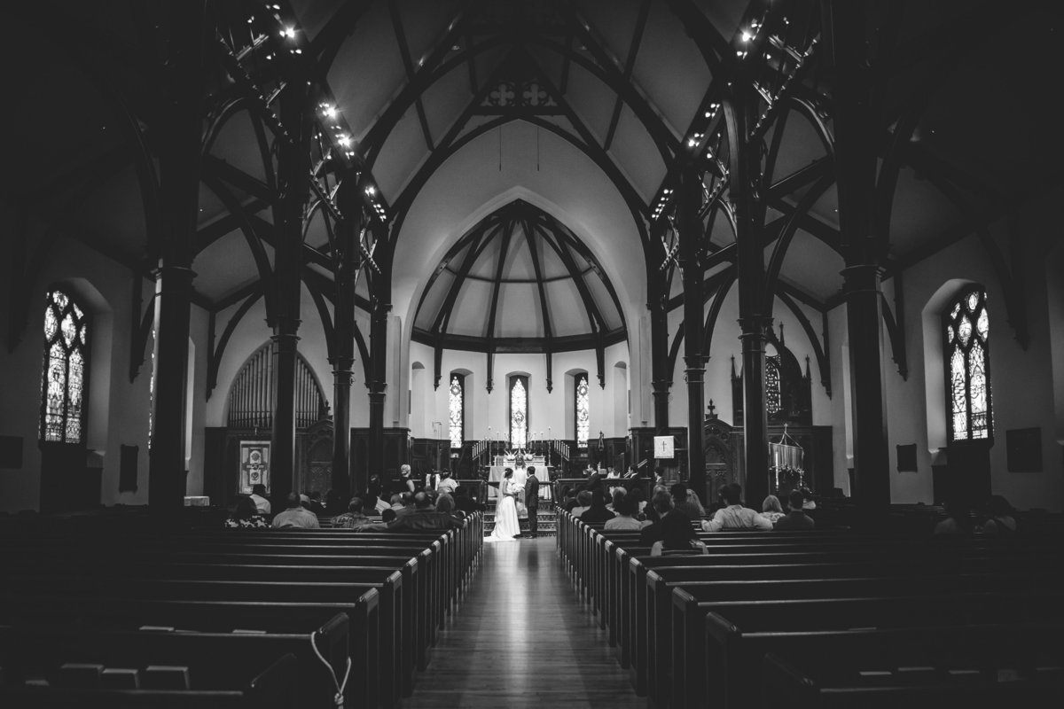 bride and groom stand at altar wide black and white portrait of wedding ceremony at St Marks Catholic Church in San Antonio