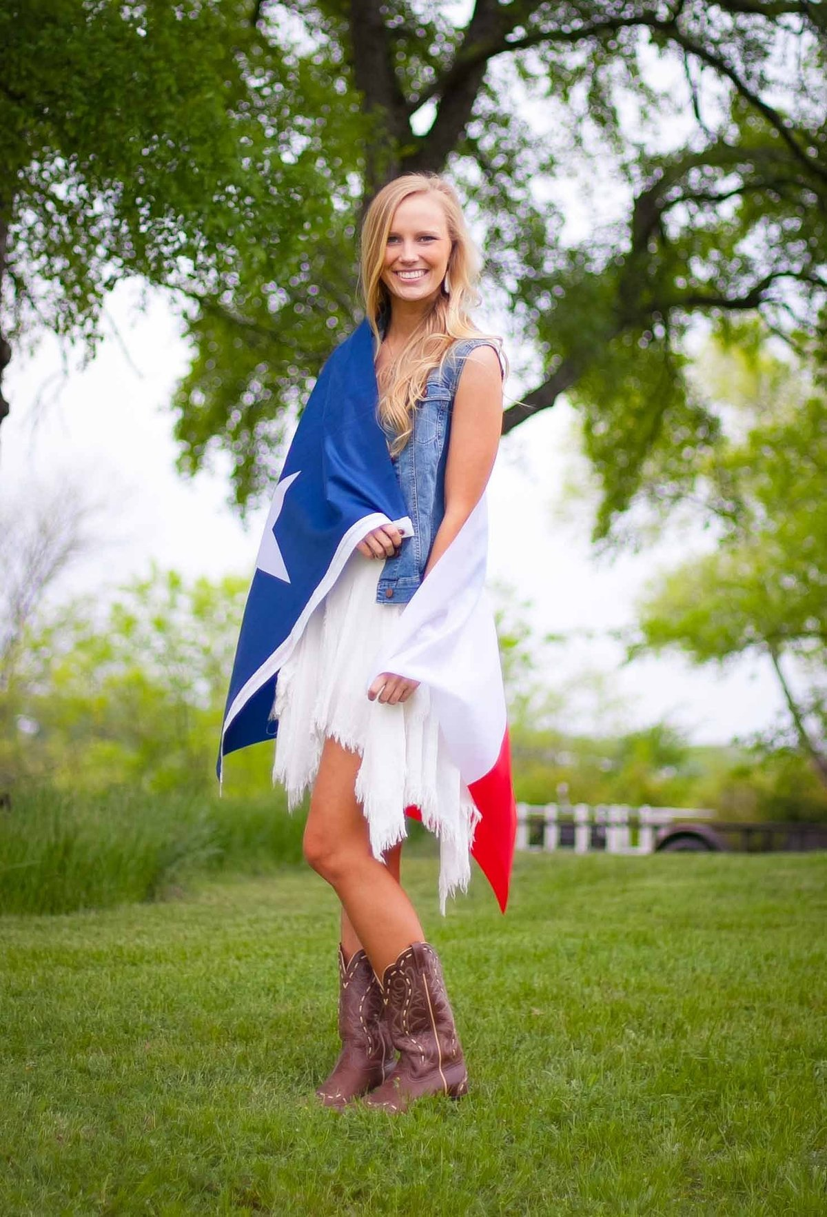 Girl wrapped in Texas Flag wearing Cowboy boots