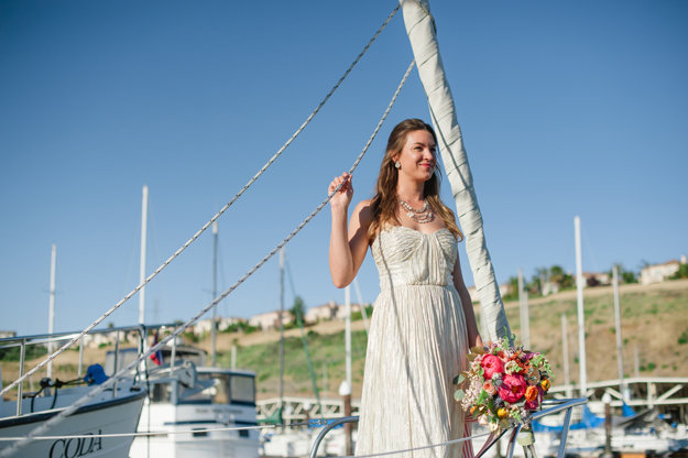 bride on a sailboat with bright florals and airbrushed makeup with a pink lip