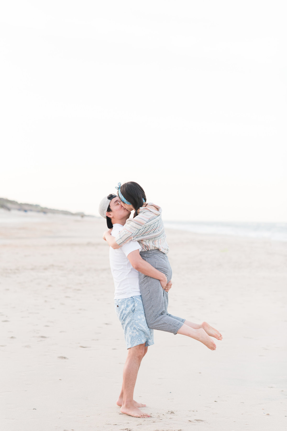 a groom holding on his bride lifting her in the air while kissing her on Corolla Beach NC