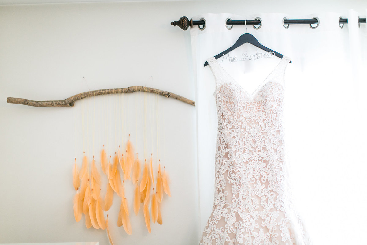 orange feathers on branch with wedding dress