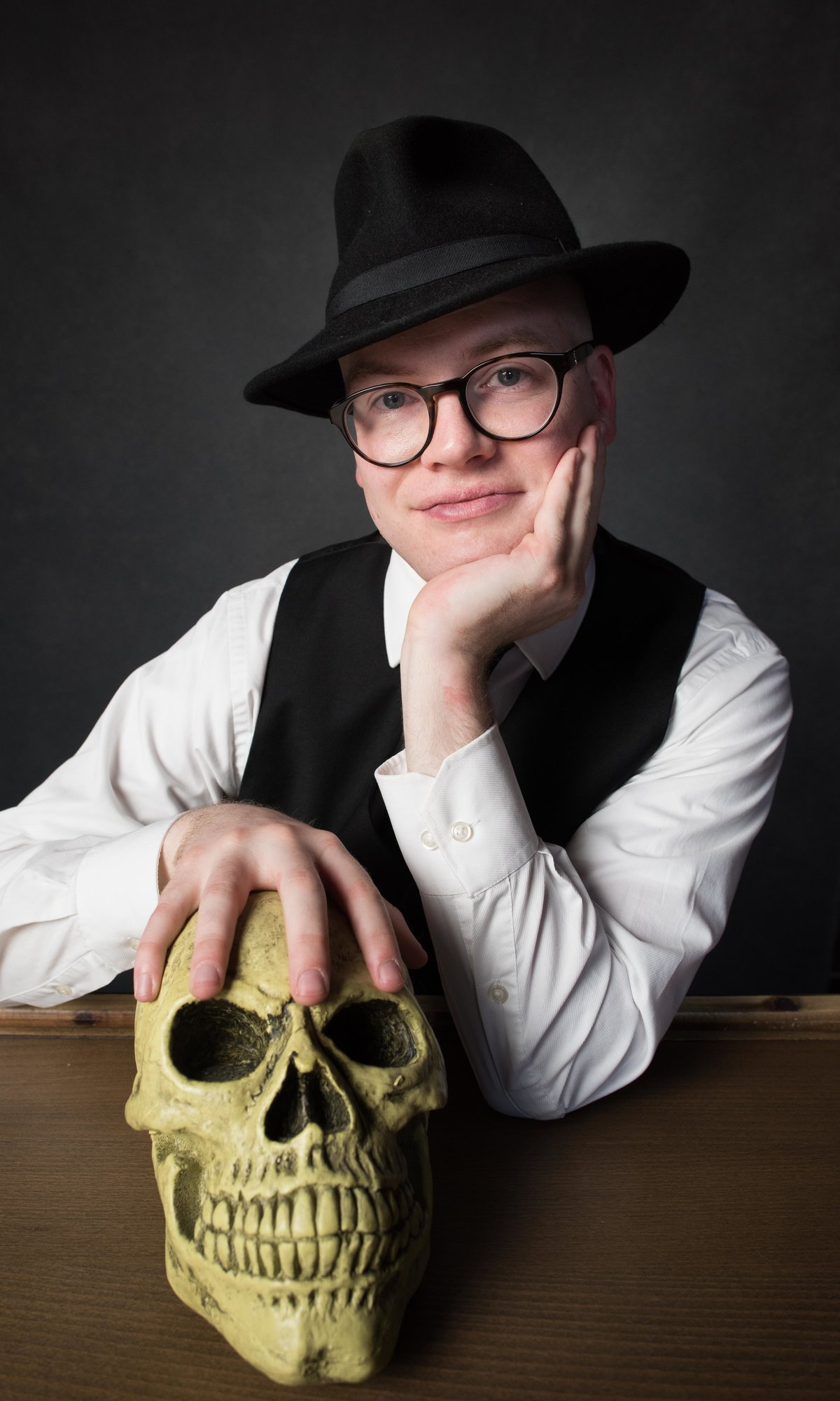 Studio portrait of Chicago author with hand resting on artificial skull.