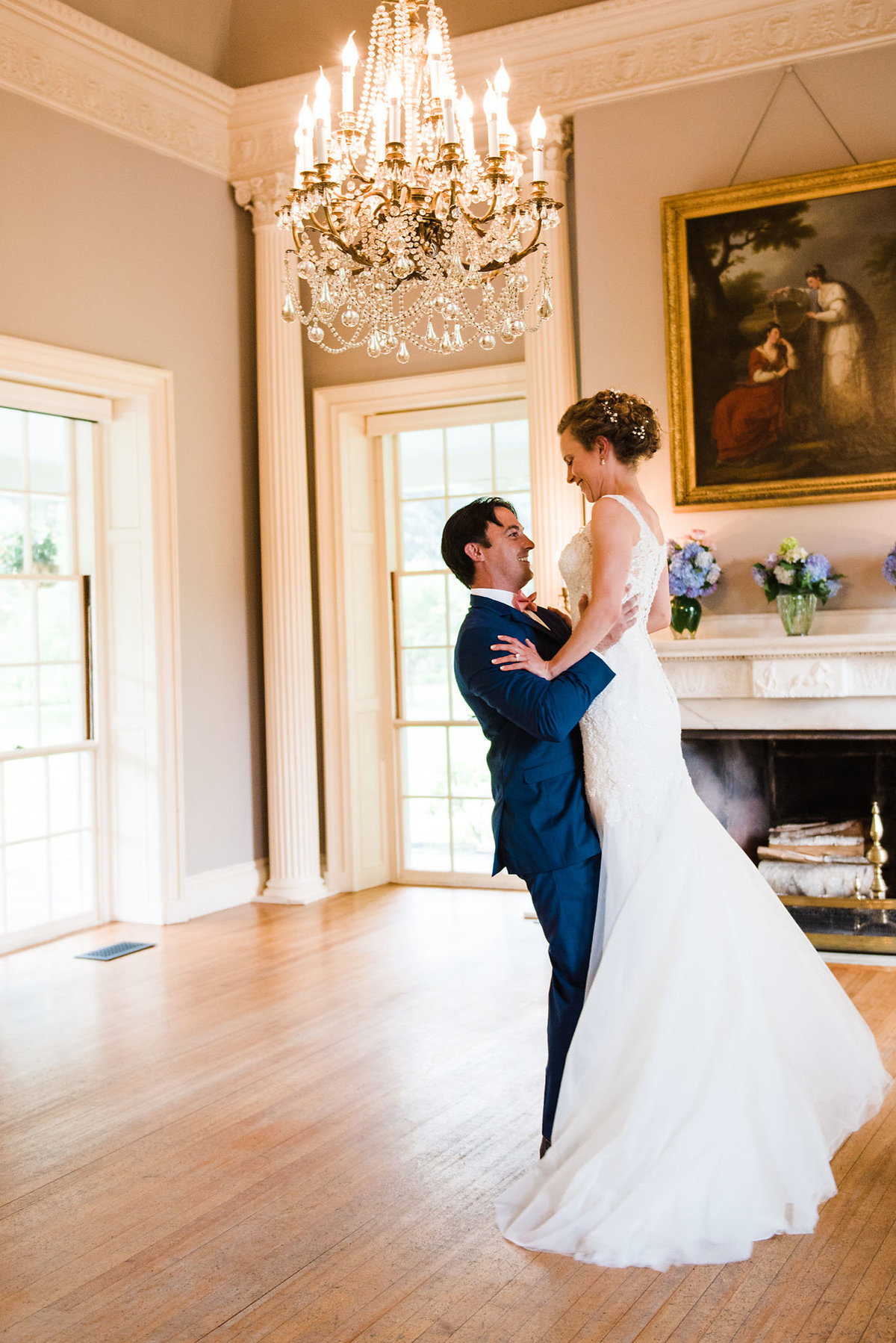 groom lifting bride, mansion wedding