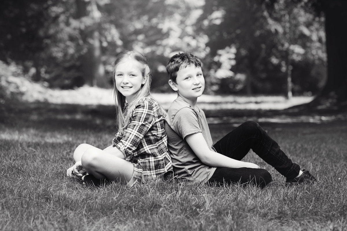 sister and brother sitting  on grass