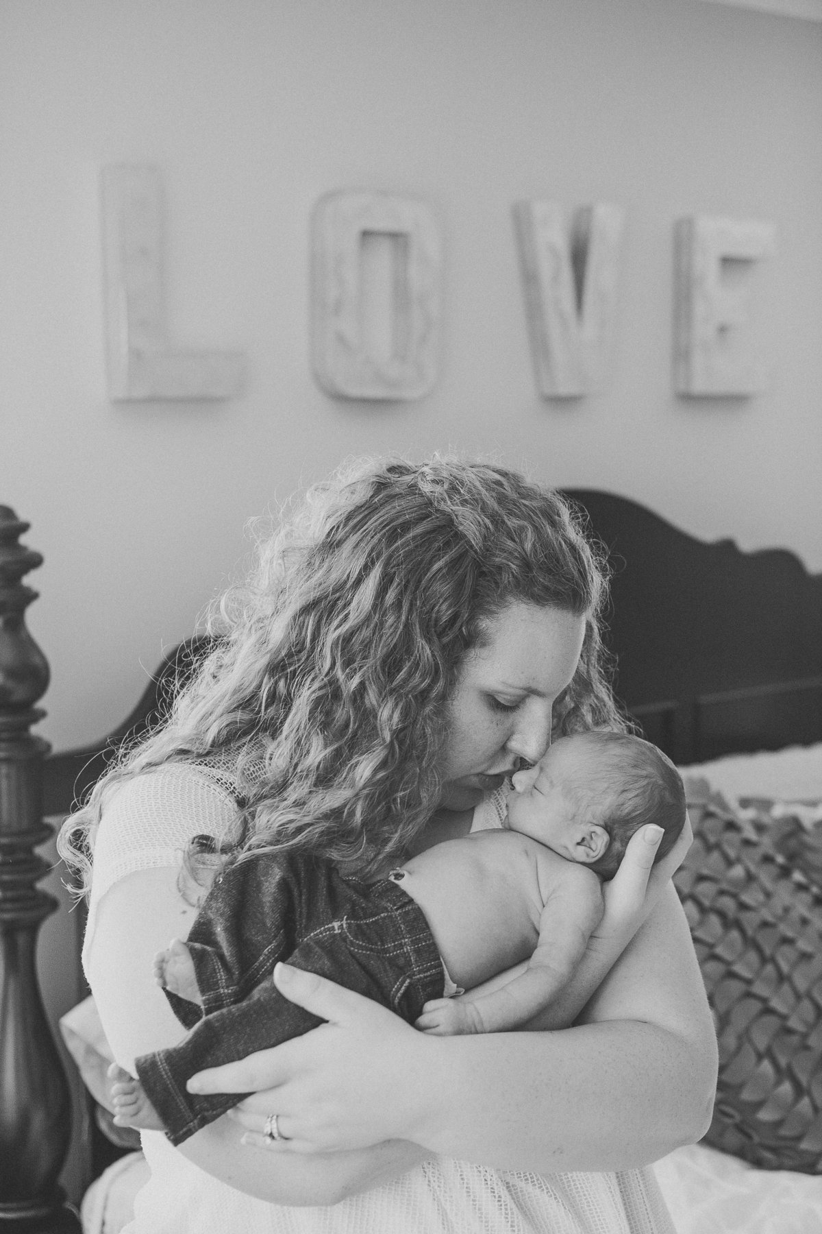 Mom kissing newborn baby boy with the word love in the background in their Florida NY home lifestyle candid photography photographer who comes to my home hudson valley NY photos