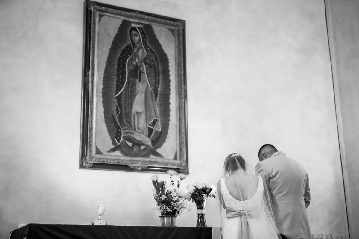 bride and groom giving roses to mary in catholic wedding ceremony at mission san jose san antonio