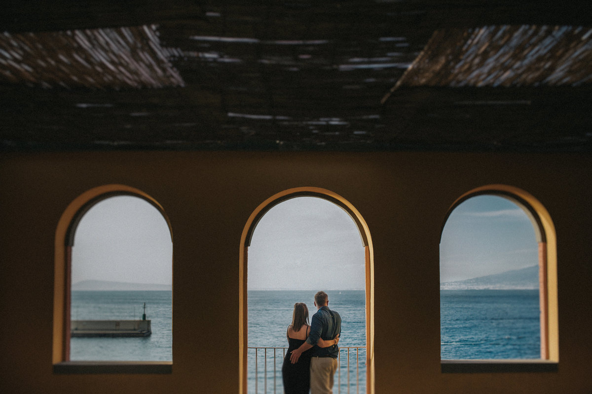 Destination Wedding Photographer Jono Symonds photographs couple hugging under an archway looking out over the Amalfi Coast, Sorrento , Italy