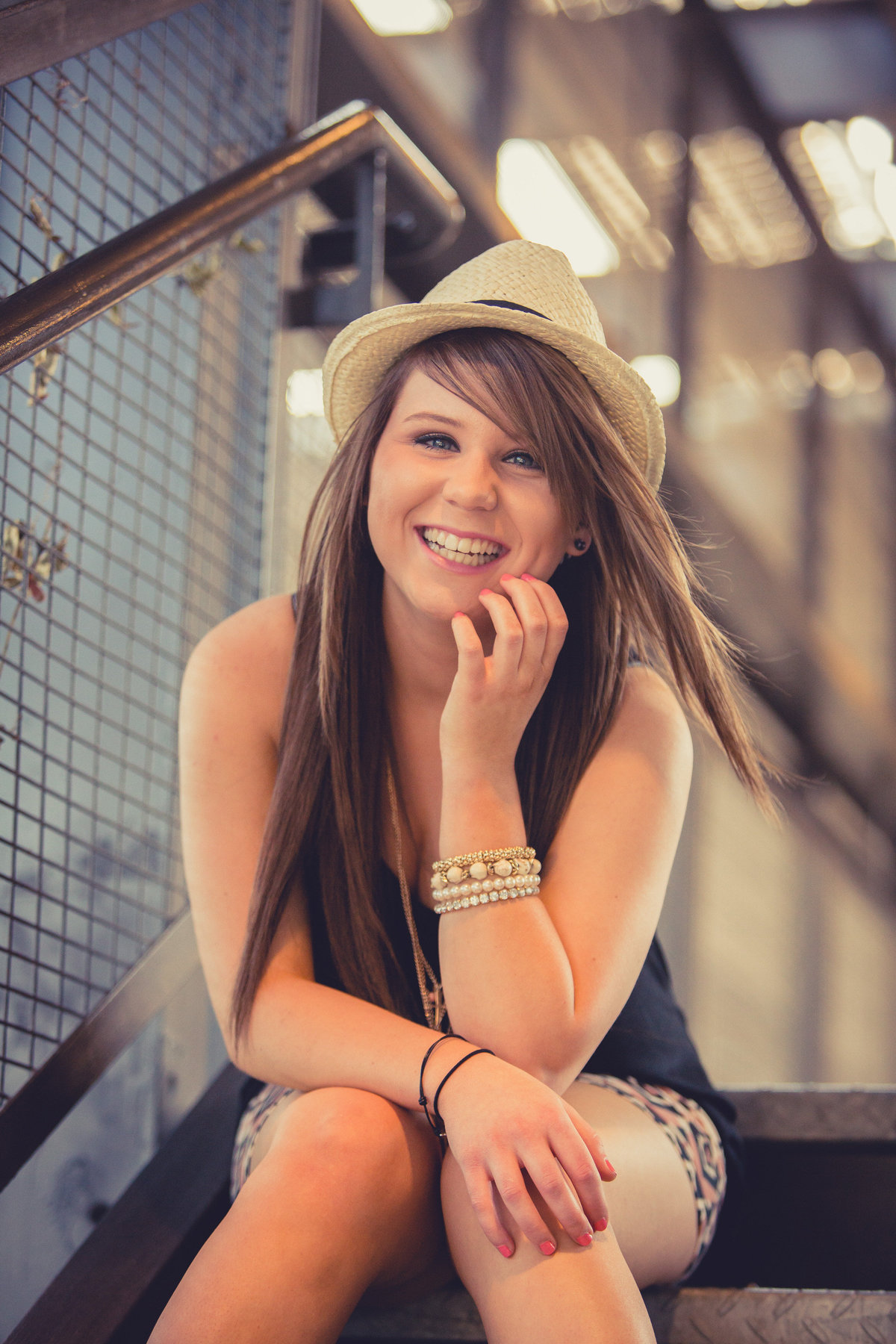 girl smiling and sitting on stairs wearing hat by San Antonio high school senior photographer