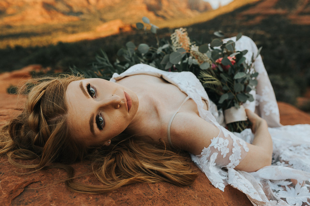 Bride laying down on the Red Rocks of Sedona, Arizona