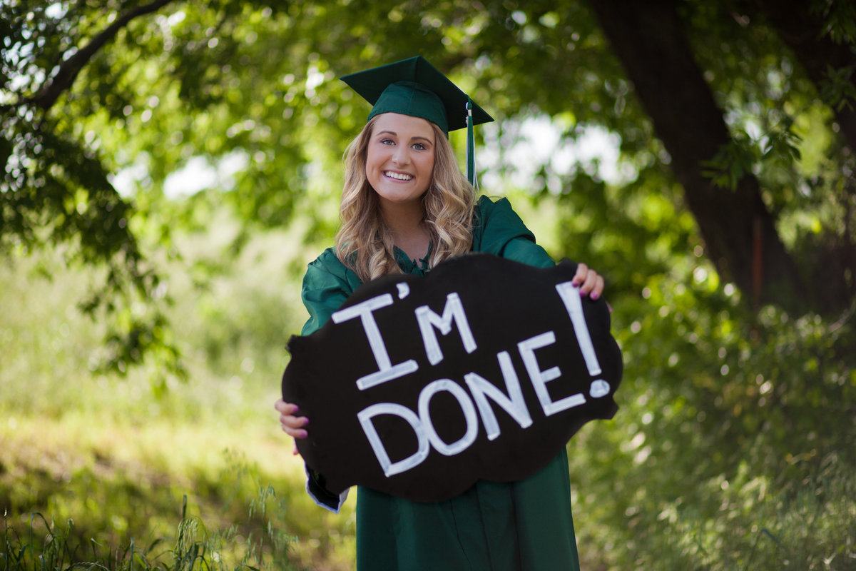 Senior girl in cap and gown with I'm Done sign in Prosper TX