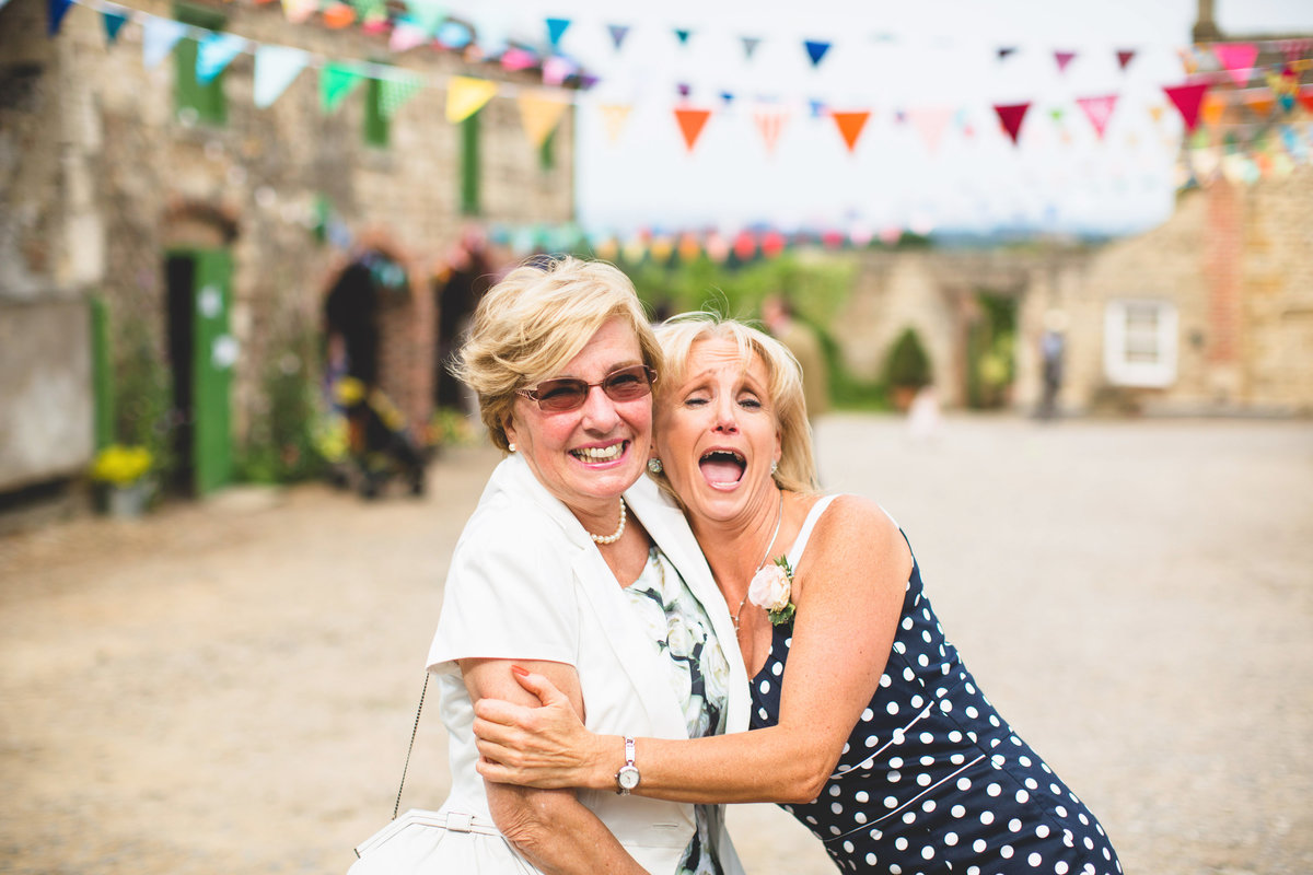 2 wedding guests laughing at vintage farm barn wedding with bunting